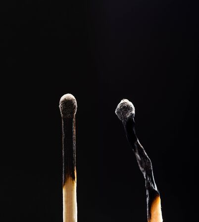 Two burned out wooden matches on black background photo