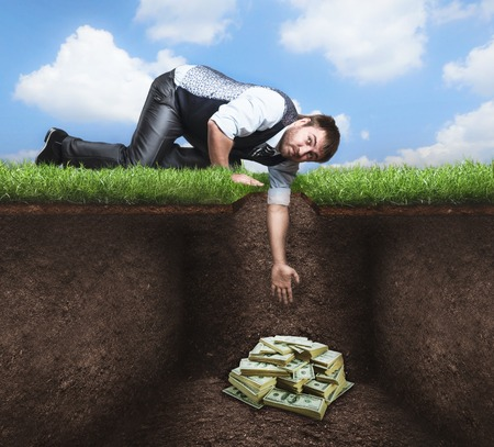 under ground: Businessman on knees tries to get treasure in the soil