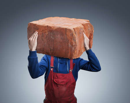 odd jobs: Man with a big brick insread of his head Stock Photo