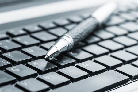 ノート パソコンのキーボードの上に黒いペン 写真素材