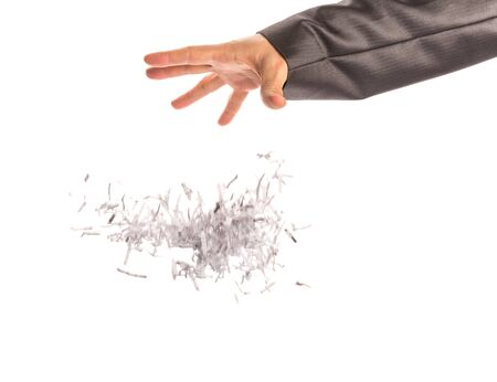 throw paper: Human hand throws a lot of little shredded sheets op papers on white Stock Photo