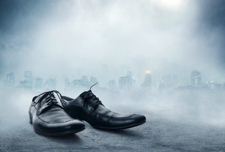 Pair of black male classic shoes against the city