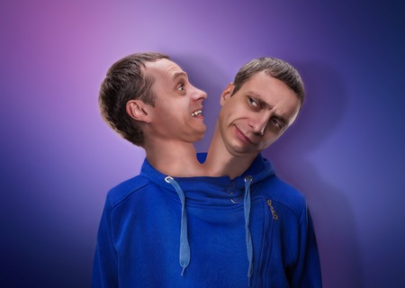 two heads: Concept of split personality, a man with two heads over blue background Stock Photo
