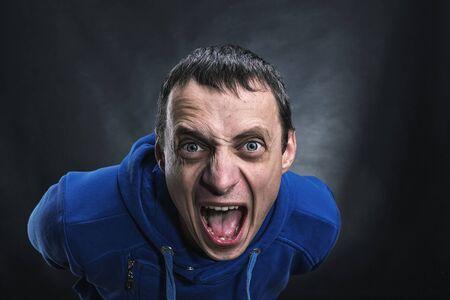 caras de emociones: Sirve la cara agresiva en la oscuridad Foto de archivo