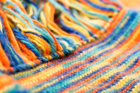 fringes: Knitted multicolored scarf with fringes closeup Stock Photo