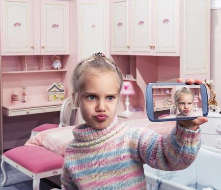 jolie petite fille: Petite fille fait des grimaces tout en faisant Selfie dans une chambre