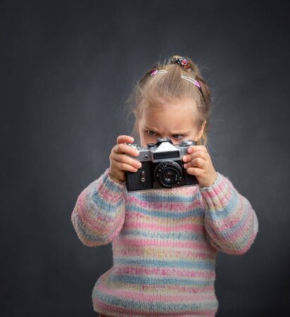 tries: Little cute girl tries to understand the retro camera