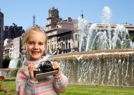 Little girl with retro camera in a city street photo