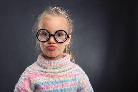 egghead: Little nerd girl in glasses makes faces over grey Stock Photo