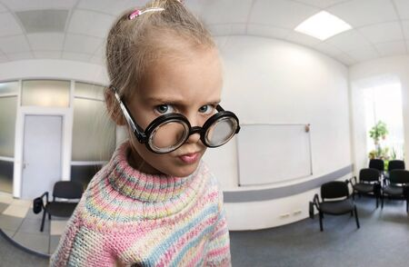 egghead: Serious little girl in glasses in the class