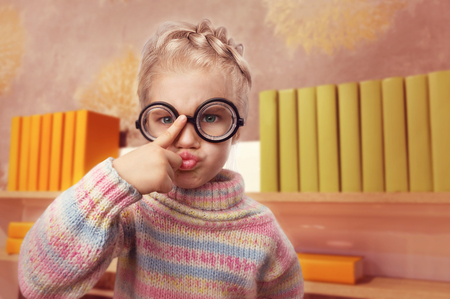 egghead: Little egghead girl in glasses makes faces in home interior Stock Photo