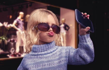 pretty little girl: Glamour little girl  doing selfie by the phone in the shopping mall Stock Photo