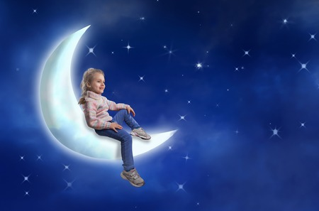 Nice little girl sits on the moon against starry sky