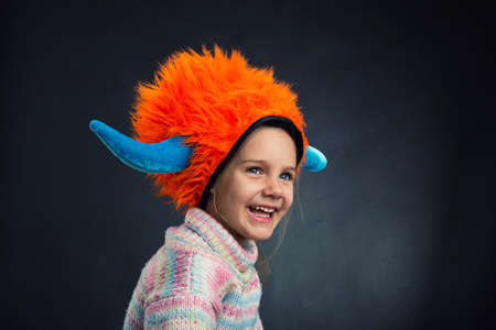 Little funny girl in party hat over dark background photo
