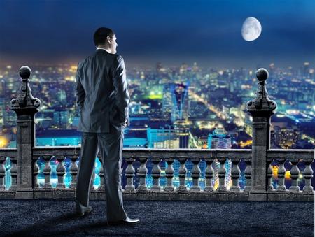 dia y noche: El hombre de negocios de pie de nuevo mira a la ciudad por la noche
