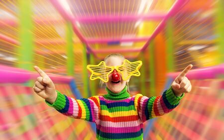 Little girl in funny party glasses in playing room photo