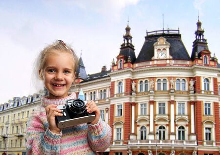 Little girl with retro camera in an European street photo