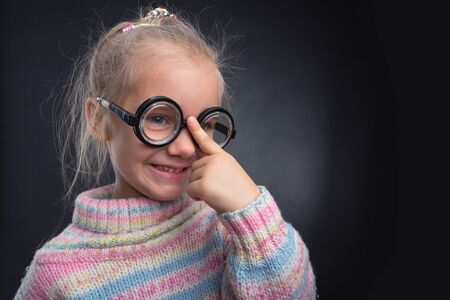 egghead: Cute nerd girl in glasses makes faces over grey