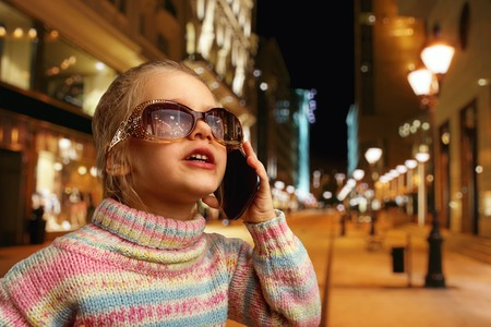 Cute little girl in sunglasses talks on phone in the street at night photo