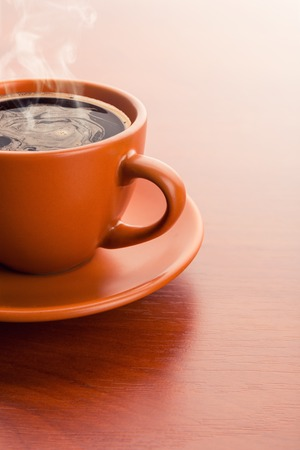 steaming coffee: Cup of hot steaming coffee on a wooden surface