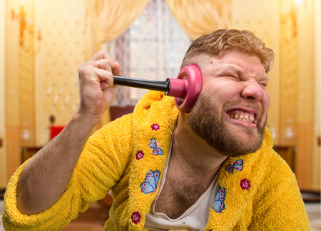 Strange man in a terry bathrobe is cleaning his ear by a plunger in his ear in home interior photo