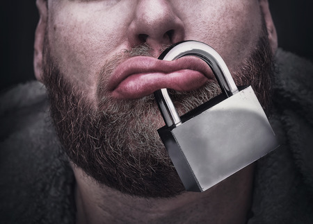 silence: Closeup of male lips with a lock