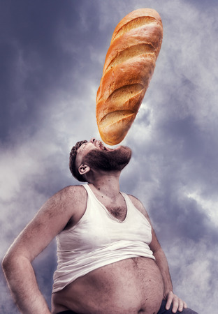 1 mature man: Fat man sits eating a huge bread over cloudy sky