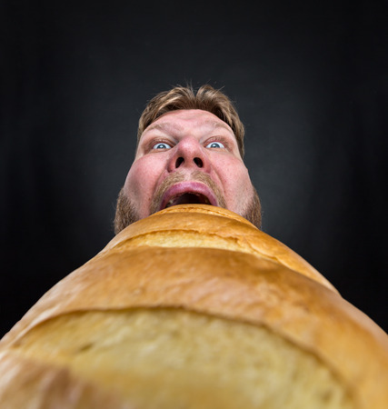 men shirt: Closeup of a man eating a huge bread over black