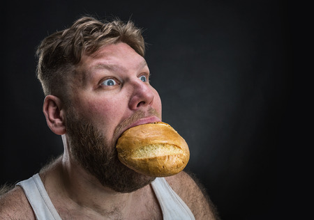 crazy guy: Side view of a man eating a big bread over black