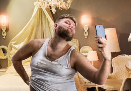Glamour ugly man with beard takes selfie in bedroom