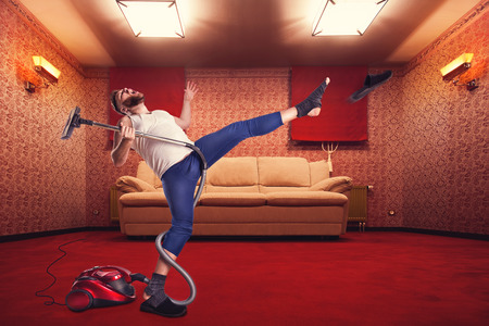 Adult man dancing with the vacuum cleaner at home interior