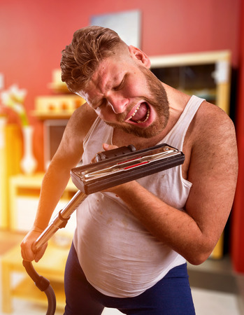hoover: Adult man with beard sings to the vacuum cleaner at home interior