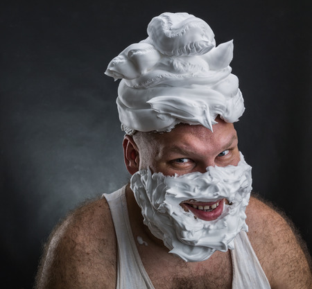 bizarre: Strange smiling man with shaving foam on his face and on his head over grey background Stock Photo