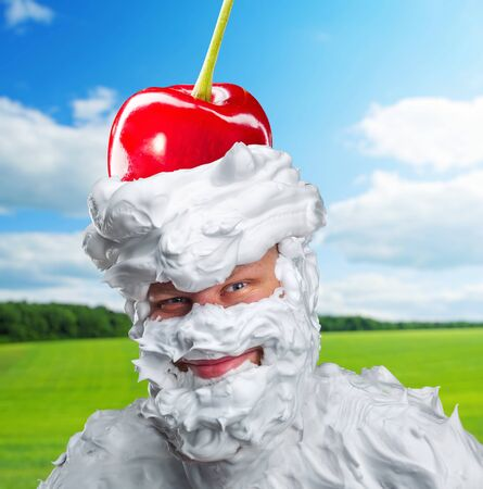 Smiling man with whipped cream and a cherry on his head over nature background
