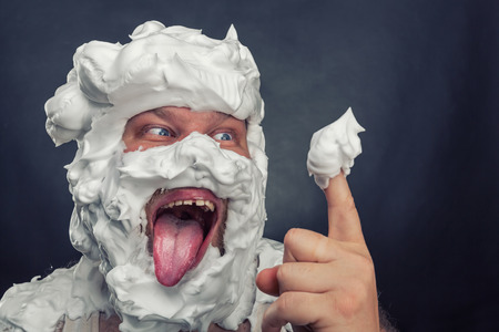 Crazy man with  whipped cream on his face is going to lick his finger Stock Photo