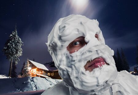 Surprised strange man with shaving foam on his face and on his head at night photo