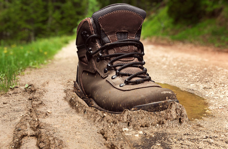Tracking boot standing on a muddy road