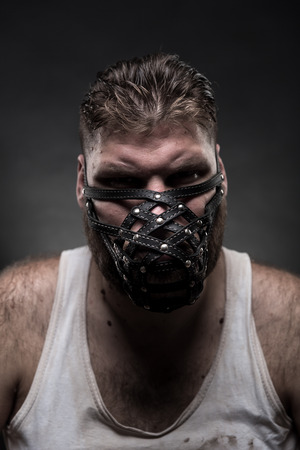 warning vest: Adult agressive man in muzzle over dark background Stock Photo