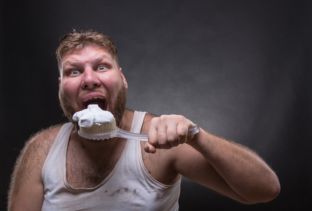 darck: Adult man cleaning teeth over darck background Stock Photo