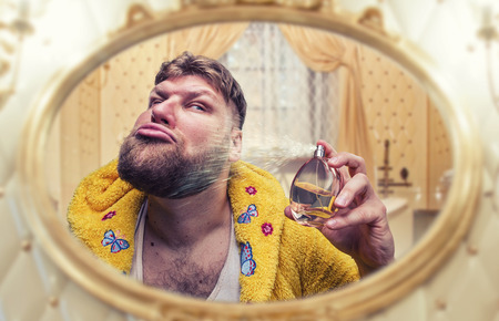 the ugly: Strange man in terry bathrobe perfumes himself looking in the mirror Stock Photo