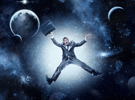 tumble down: Businessman falling in space against planets and stars