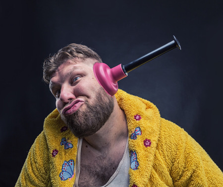 odd: Strange man in a terry bathrobe with a plunger in his ear Stock Photo