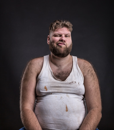 Fat unhappy man with beard in dirty shirt over dark background
