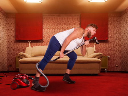 vacuum: Adult man sings to the vacuum cleaner at home interior