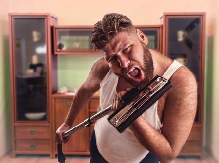 householder: Funny man with beard sings to the vacuum cleaner at home interior Stock Photo