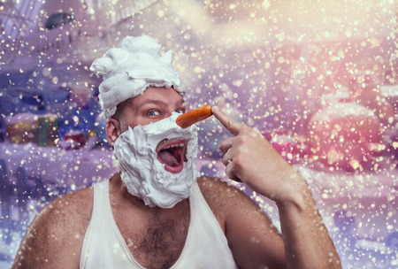 one mature man: Smiling man with shaving foam points at his carrot nose over winter background