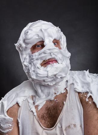 Bizarre man met gezicht volledig in scheerschuim denkt over grijs Stockfoto