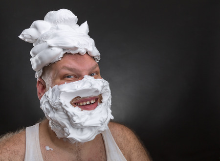 Bizarre smiling man with shaving foam on his face and on his head over grey background