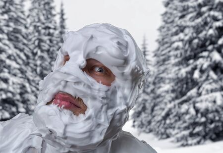 Surprised strange man with shaving foam on his face and on his head over in winter forest photo