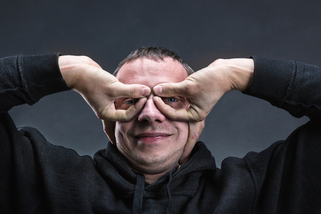 forming: Man forming glasses with his hands over grey
